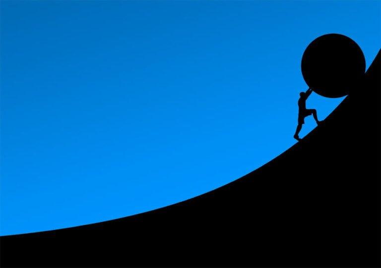 En man som rullar en sten uppför en backe