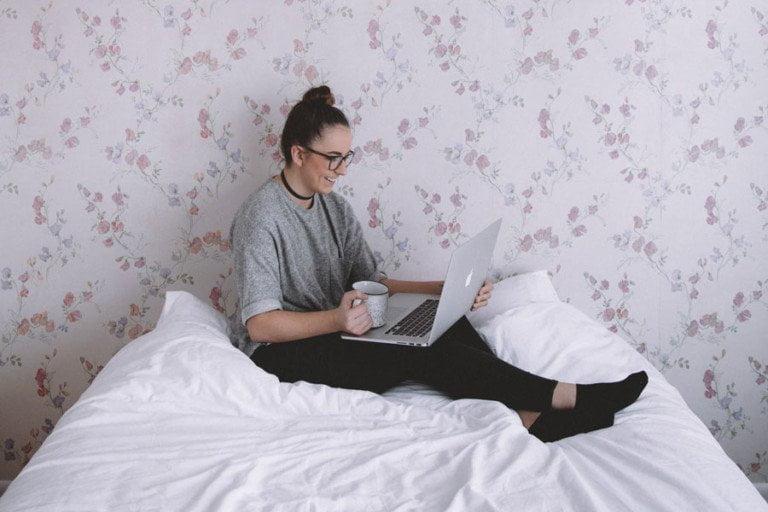 Kvinna som sitter på en säng med laptop och en kopp kaffe