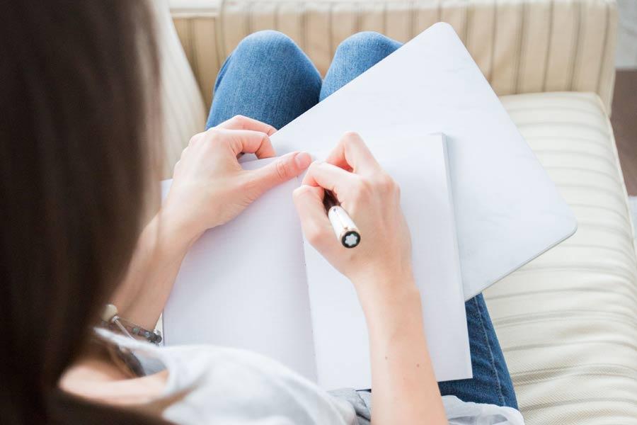 Kvinna som skriver ned sina mål i en skrivbok
