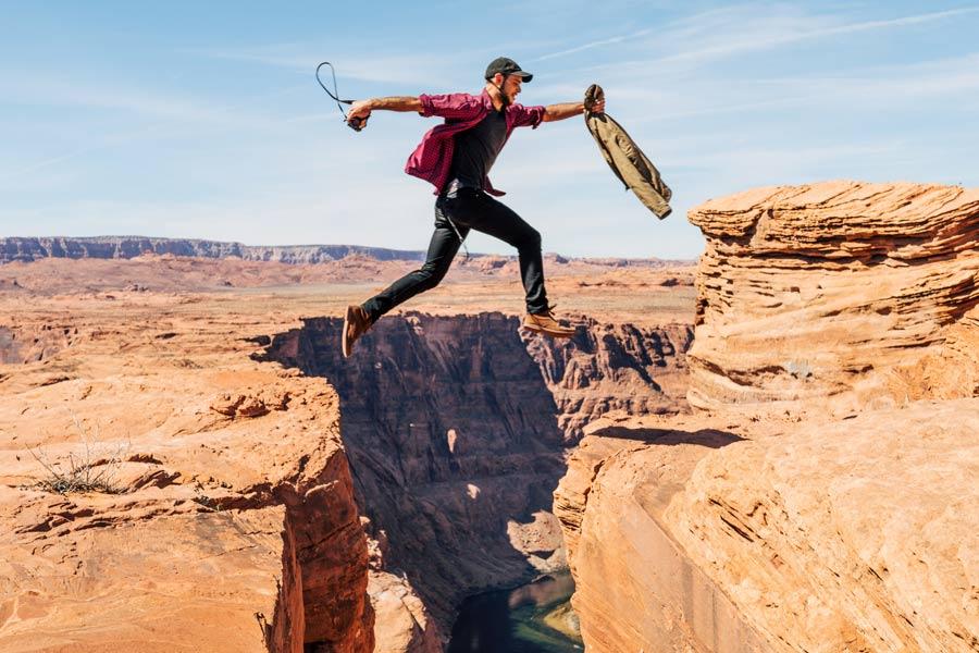 Motiverad man som hoppar över en bergsklyfta