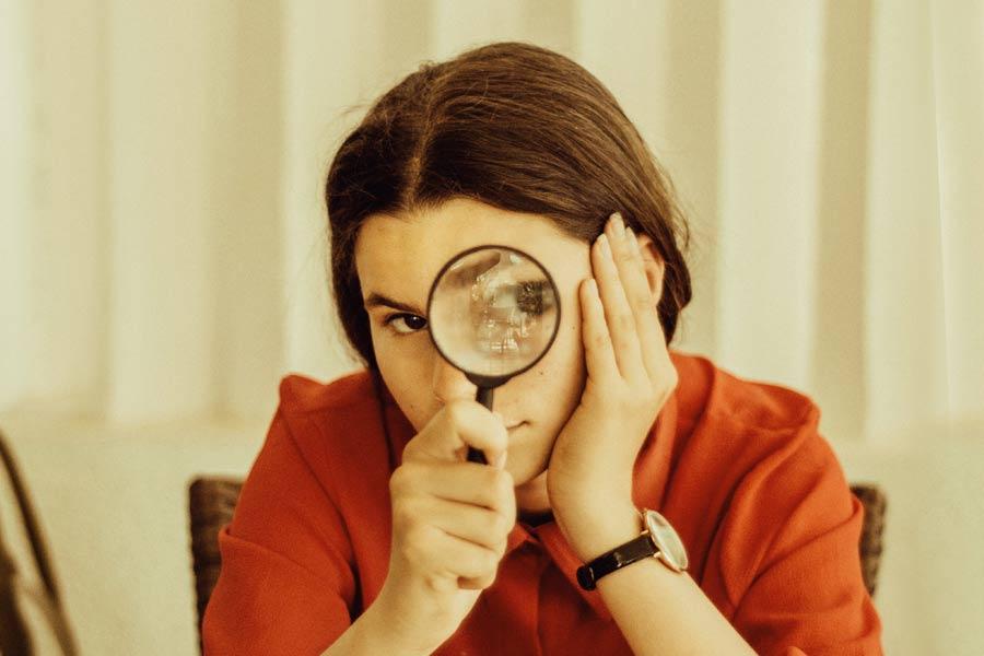 Flicka med förstoringsglas som söker meningsfullhet i livet